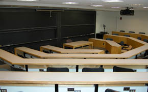 A large classroom with tiered seating, several chalkboards, and a projector.
