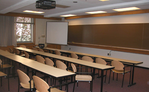 A typical classroom with rows of seats, as well as chalkboards and a projector screen at the front of the class.