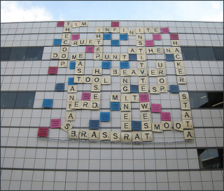 On the side of a building hang multi-colored squares, each with a letter or phrase on them, simulating a Scrabble game.