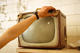 A hand turns on a small vintage television set.