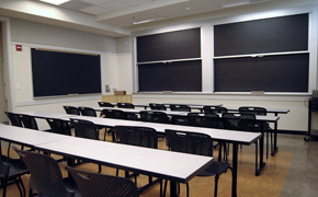 A functional classroom, with long tables, chairs, and lots of black boards.