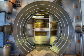 The opening of a bank vault that has metal bars surrounded by a metal circle.
