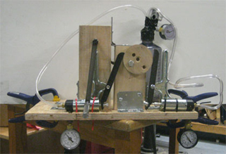 A hand-powered vacuum pump features a wooden flywheel that connects to two commercial vacuum pump units, mounted on a wooden frame.