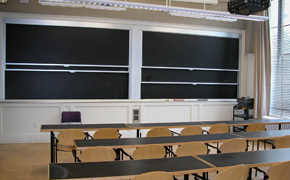 This classroom contains rows of long tables, with each row having roughly six chairs behind it. At the front, there are two columns of sliding chalkboards.