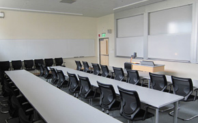 Photo of a high-ceiling classroom with long row tables for students and whiteboards on both the front and side walls.