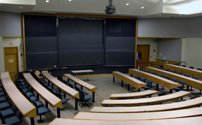 A view of the classroom from the back, facing the blackboards in the front of the room.
