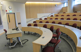 A raked, amphitheater-style lecture hall with five rows of seating and a lectern in front.